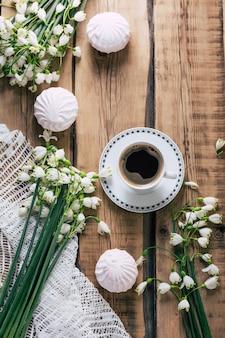 スノー ドロップの花と木製のテーブルの上のコーヒー カップのトップ ビュー