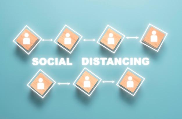 木製キューブブロックの白い人アイコンの社会的距離の平面図です。 covid-19と新しい通常のコンセプト。