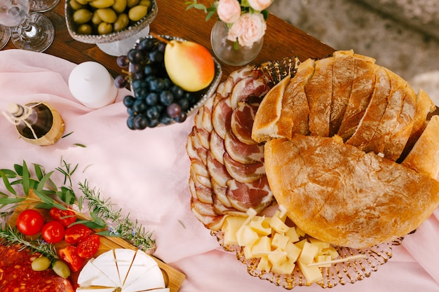 분홍색 흐르는 천에 있는 접시에 라드와 단단한 치즈를 곁들인 햄을 곁들인 부드럽고 신선한 빵