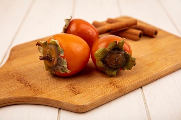 白い木の表面にシナモンスティックと木製のキッチンボード上の柔らかい柿の上面図
