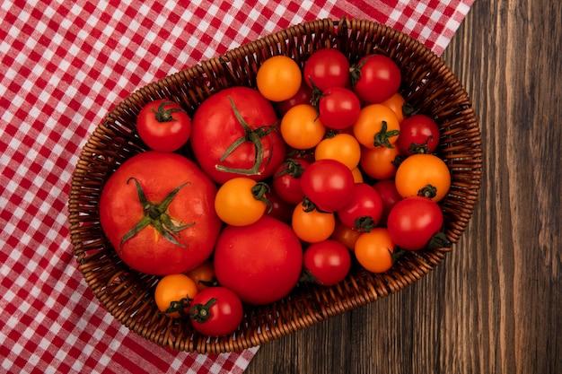 木製の表面のチェックされた布の上のバケツの上の柔らかい赤とオレンジ色のトマトの上面図