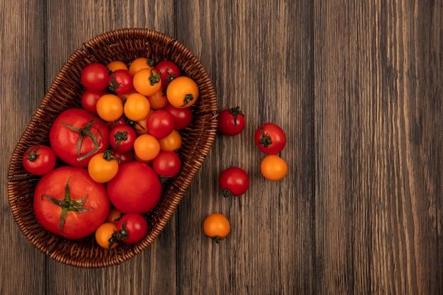 복사 공간이 나무 표면에 양동이에 부드러운 붉은 색과 오렌지색 토마토의 상위 뷰