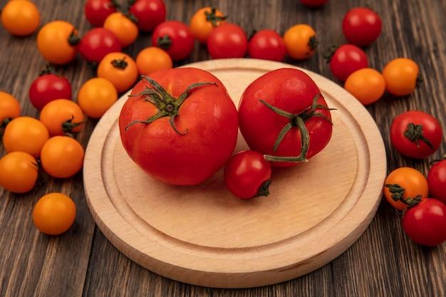 木製の壁に分離されたチェリートマトと木製のキッチンボード上の柔らかい赤いトマトの上面図