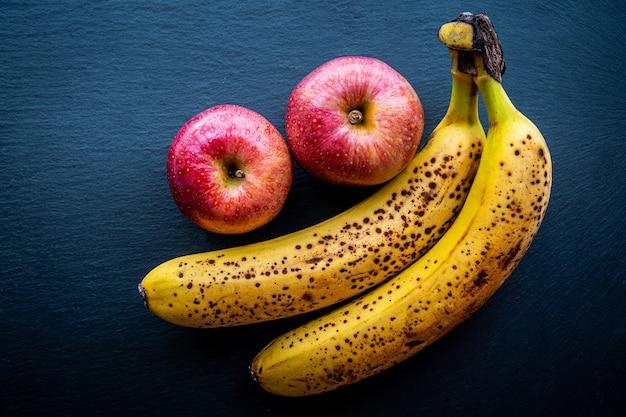 暗い背景にいくつかのバナナとリンゴの平面図健康と自然食品の概念。