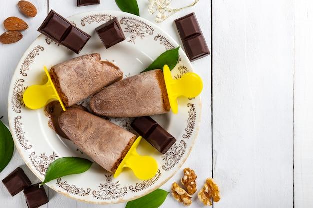자연에서 온 초콜릿, 견과류, 아몬드, 잎으로 덮인 흰색 나무 테이블에 있는 빈티지 접시에 있는 맛있고 상쾌한 초콜릿 아이스크림 롤리의 꼭대기