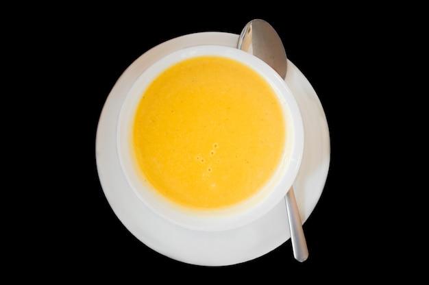 白いボールと黒の背景にプレートに役立つスープのトップビュー