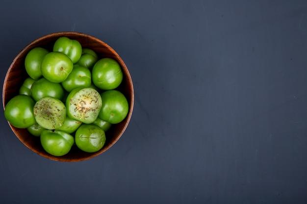 복사 공간 블랙 테이블에 나무 그릇에 신 녹색 자두의 상위 뷰