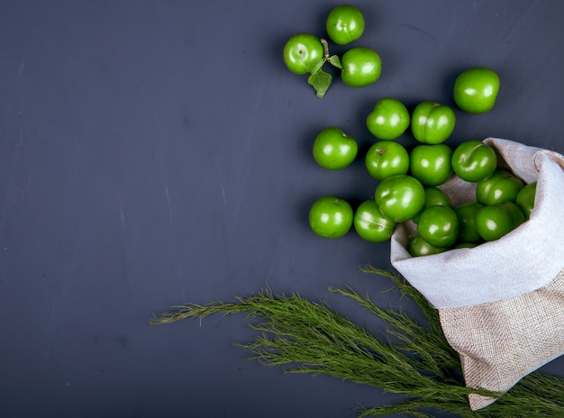 복사 공간이 검은 테이블에 자루에서 흩어져 신 녹색 자두의 상위 뷰