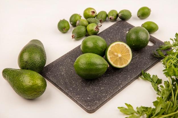 Вид сверху кислого лайма на кухонной доске с фейхоа и авокадо, изолированными на белой стене