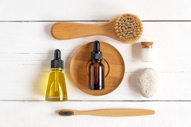 Вид сверху космических инструментов и косметики для кожи. массажные и зубные щетки, эфирные масла, морская соль, камни на белом деревянном столе. концепция нулевых отходов.