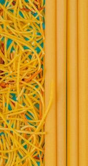 青い表面にスパゲッティとブカティーニのトップビュー