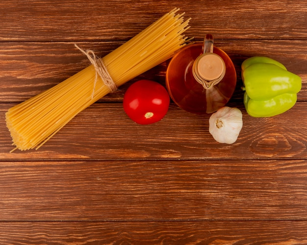 コピースペースを持つ木材にトマトガーリックピーマンと溶かしバターのスパゲッティパスタのトップビュー