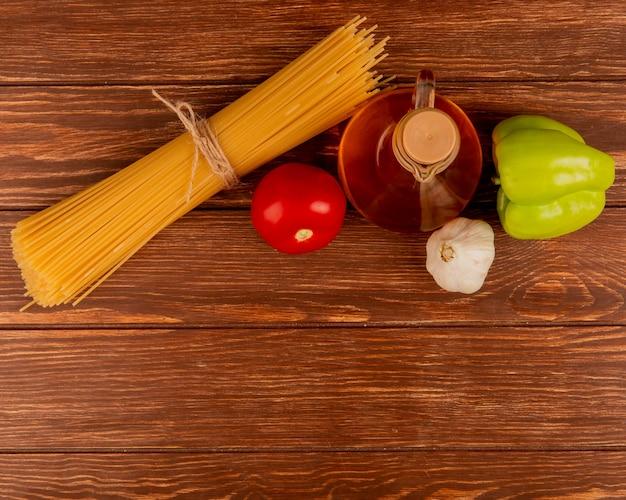 コピースペースを持つ木製の表面にトマト、ニンニク、コショウ、溶かしバターのスパゲッティパスタのトップビュー
