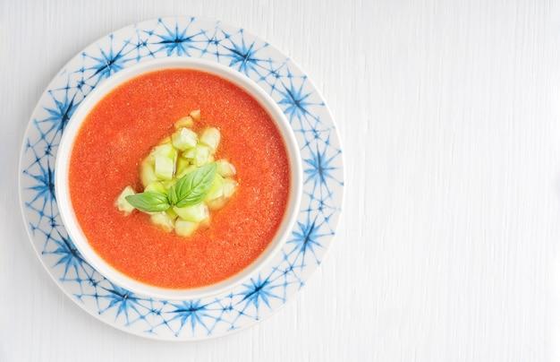 Вид сверху испанского гаспачо холодный томатный суп из сырых овощей на белом деревянном столе