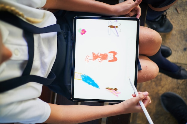 Вид сверху испанской школьницы, рисующей на планшете в парке