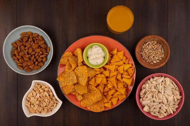 オレンジ色の皿にスパイシーなクリスピーチップスの上面図、ボウルにソース、木製のボウルにヒマワリの種、松の実、木製のテーブルにオレンジジュースのグラス