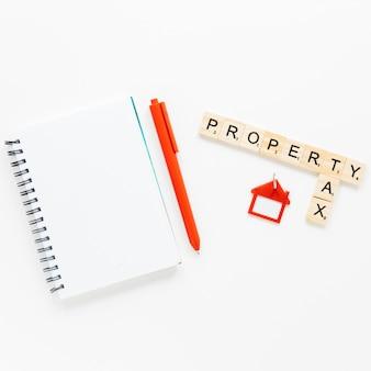 白い背景で隔離の財産と税のテキストを持つ木製のブロックの近くのスパイラル日記のトップビュー