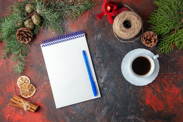 펜 전나무 브랜치 계피 라임 침엽수 콘과 어두운 배경에 홍차 한 잔이 있는 나선형 노트북의 상위 뷰