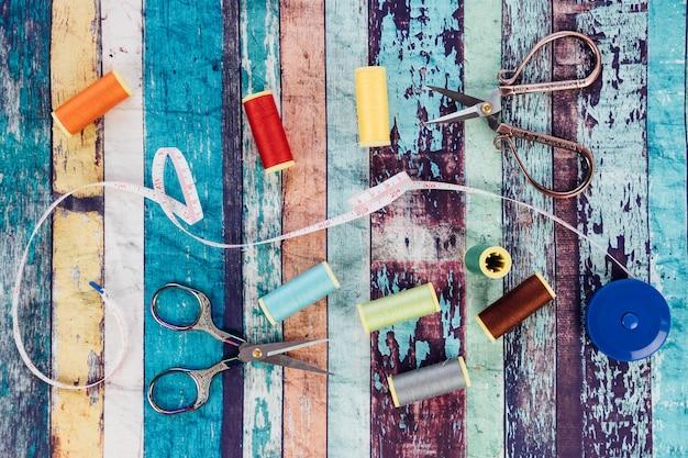 색 실의 스풀, 재봉 테이프 측정 및 양장사의 가위의 상위 뷰.