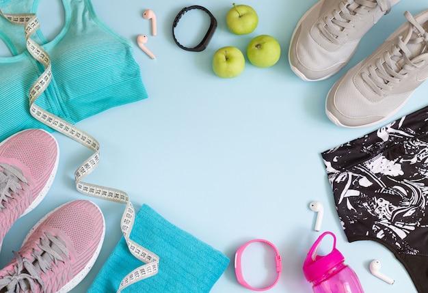 Вид сверху спортивные аксессуары с копией пространства. кроссовки, бюстгальтеры, бутылка, наушники, полотенце, рулетка на синем фоне