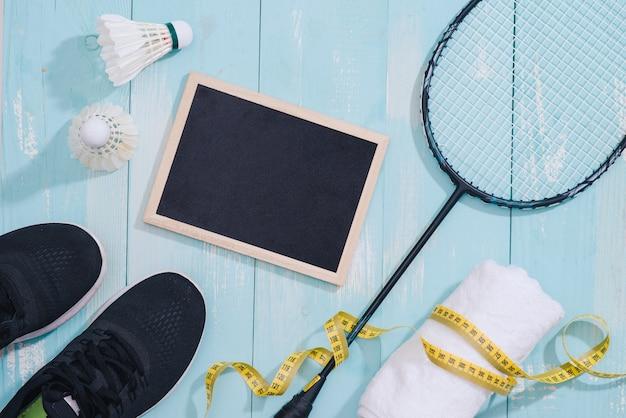 Вид сверху спортивного оборудования, часов, рулетки, обуви, бутылки с водой, полотенца, ракетки для бадминтона и волана, концепции здорового образа жизни и фитнеса