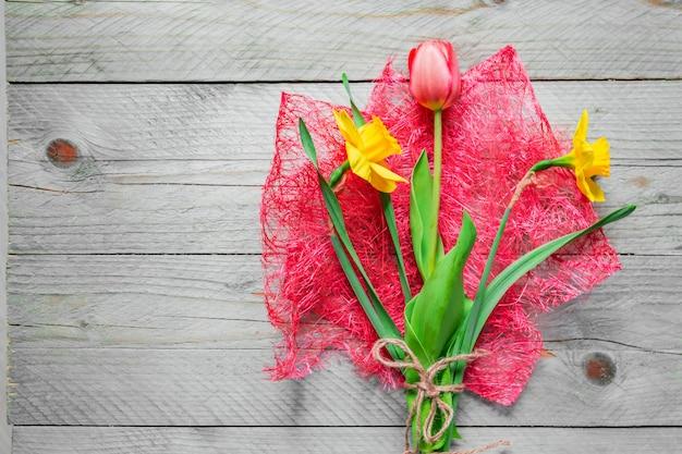봄 꽃 꽃다발의 상위 뷰입니다. 노란 수 선화와 나무 테이블에 핑크 튤립. 공간을 복사하십시오.