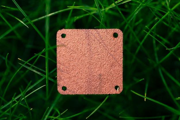 ロゴタグ付きの芝生の緑の草の衣類の創造的なレイアウトのための正方形の茶色の革パッチの上面図。