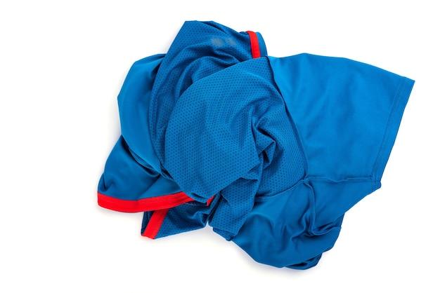 Вид сверху стога или кучи синей футболки, изолированные на белом фоне.