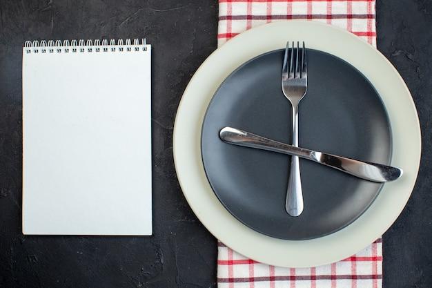 검은색 바탕에 여유 공간이 있는 빨간색 벗겨진 수건 노트북에 있는 짙은 회색 색상과 흰색 빈 접시에 설정된 스테인리스 칼 붙이의 상단 보기