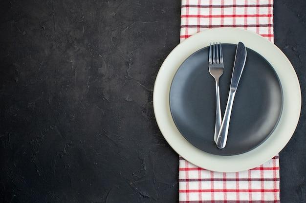 여유 공간이 있는 검정색 배경에 빨간색 벗겨진 수건에 짙은 회색 색상과 흰색 빈 접시에 설정된 스테인리스 칼 붙이의 상단 보기