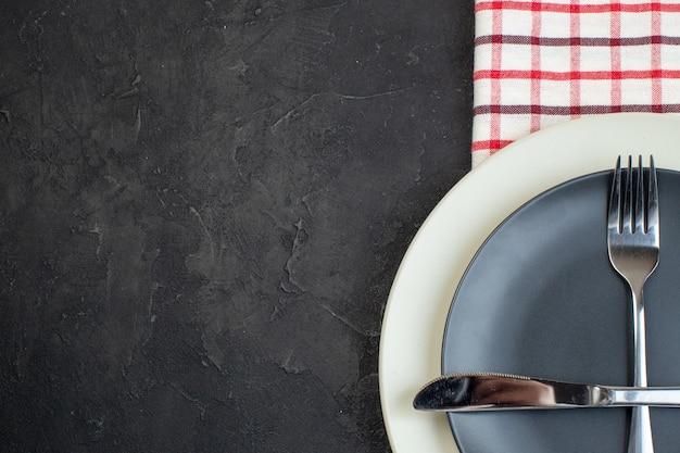 검은색 바탕에 빨간색 벗겨진 수건에 짙은 회색 색상과 흰색 빈 접시에 설정된 스테인리스 칼 붙이의 상단 보기