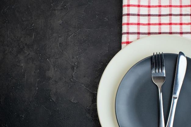 검은색 바탕에 여유 공간이 있는 왼쪽에 빨간색 벗겨진 수건에 짙은 회색 색상과 흰색 빈 접시에 설정된 스테인리스 칼 붙이의 상단 보기