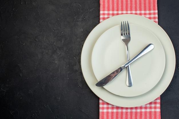 여유 공간이 있는 검정색 배경에 빨간색 벗겨진 수건에 흰색 빈 접시에 설정된 스테인리스 칼 붙이의 상위 뷰