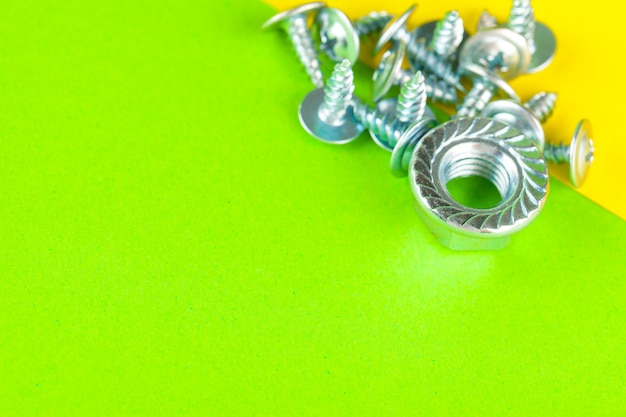 밝은 녹색 배경에 스테인레스 스틸 볼트 또는 철 손톱의 상위 뷰