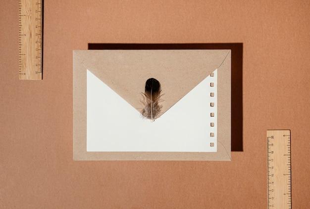 Вид сверху канцелярского конверта с пером