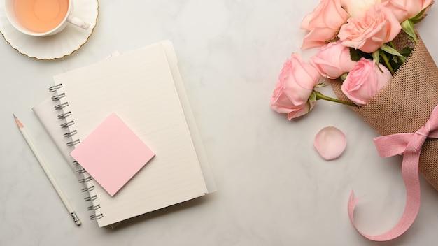 ホームオフィスルームのバラのブランチとコーヒーカップと大理石のテーブルの上の文房具の上面図