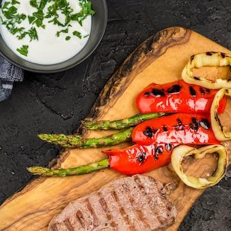 Вид сверху стейк с соусом и овощами