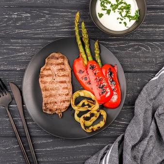 Вид сверху стейк с овощами и соусом