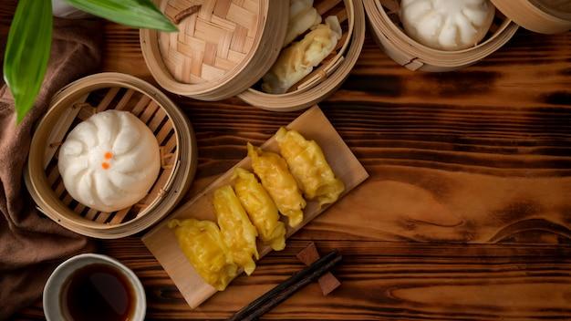 木製のテーブルに熱いお茶と竹シーマーで蒸し餃子のトップビュー