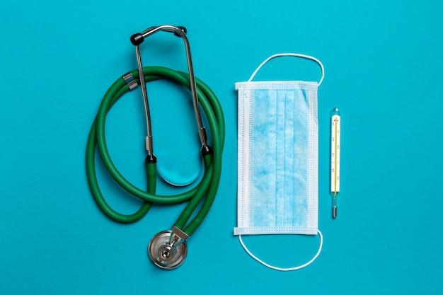 화려한 배경에 청진 기, 수은 온도계 및 보호 얼굴 마스크의 최고 볼 수 있습니다. 의료 기기 및 건강 관리 개념