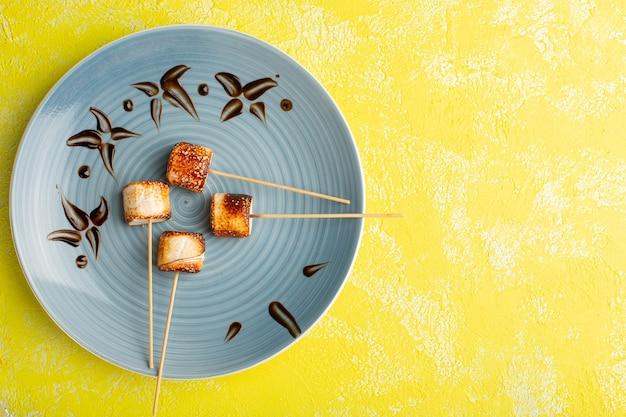 Вид сверху конфитюр из палочек внутри синей тарелки на желтом полу