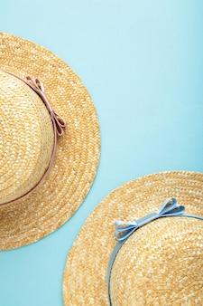 青いパステル調の表面に異なるリボンのわらのビーチ帽子の上面図