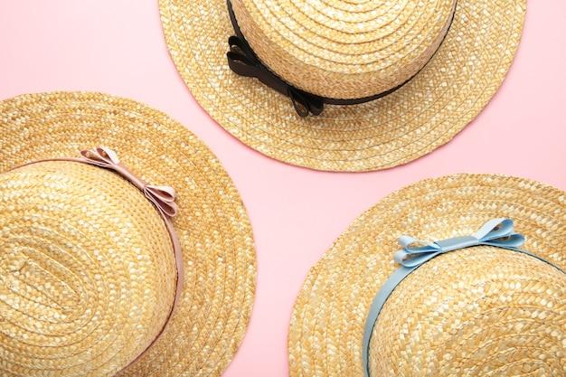 ピンクのパステルカラーの表面に異なるリボンのわらのビーチ帽子の上面図