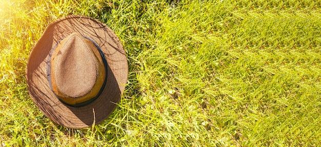 テキストのコピースペースと晴れた夏の時間のバナーの緑の芝生の上の麦わら帽子のクローズアップの上面図