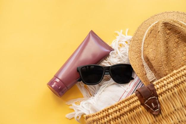 노란색 벽에 밀짚 모자 태양 안경 자외선 차단제 크림과 밀짚 비치 가방의 상위 뷰