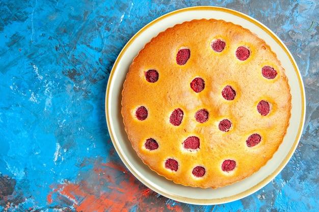 青い表面の楕円形のプレート上のストロベリーケーキの上面図