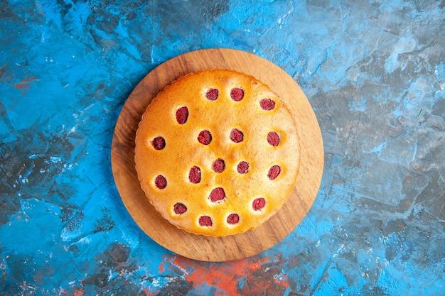 Вид сверху клубничного торта на деревянной доске на синей поверхности