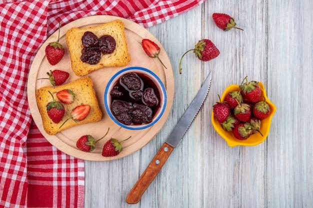 灰色の木製の背景に黄色のボウルにナイフと新鮮なイチゴとナイフで木製キッチンボードに新鮮なイチゴとボウルにいちごジャムのトップビュー