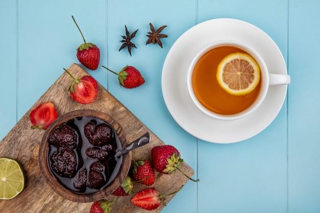 青色の背景にお茶のカップと新鮮なイチゴの木製キッチンボード上の木製ボウルにいちごジャムのトップビュー