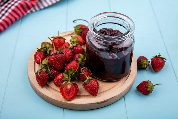 파란색 배경에 나무 주방 보드에 신선한 딸기와 딸기 잼의 상위 뷰